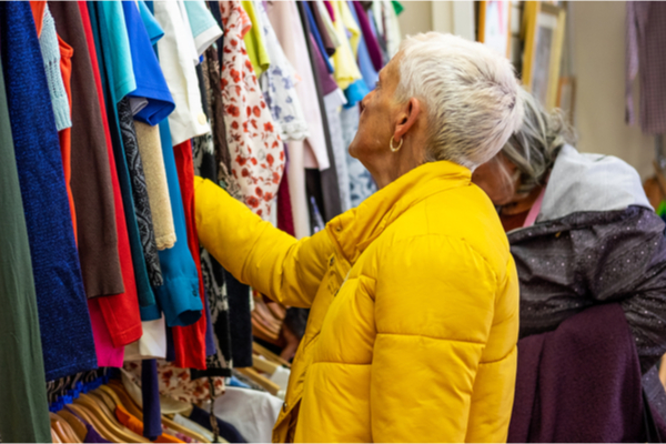 Elderly woman looking at clothes on a rack