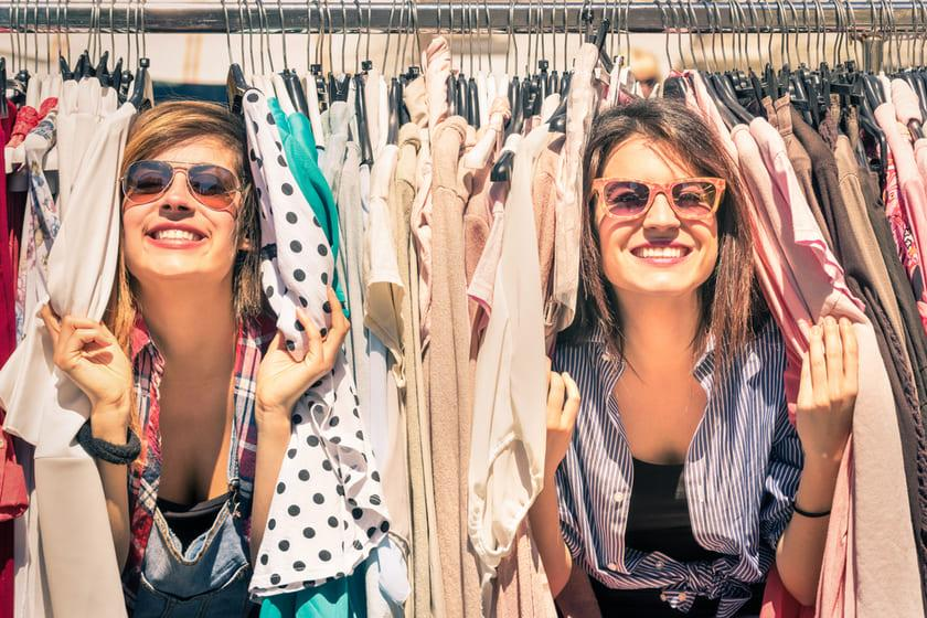 Two happy women playing in clothing rack